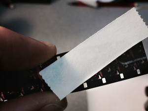 Paper tape is used to remove the dried residue from the film.