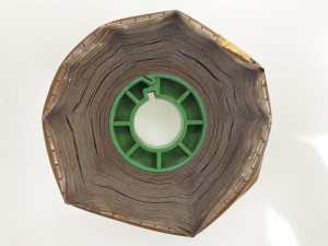 16mm magnetic soundtrack which had been fused shut, like a hockey puck, due to deterioration. Notice the warping and buckling of the film, as well as the crystallization.